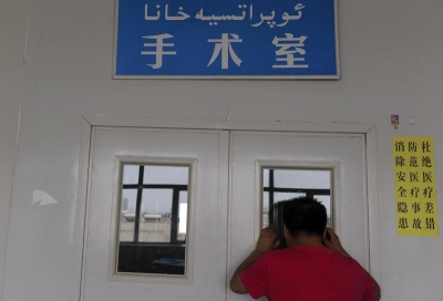 A man looks through a window on the door of an operating room as his wife undergoes a caesarean section at a hospital in Shaya county, Xinjiang Uighur Autonomous Region June 4, 2012. © 2012 Reuters