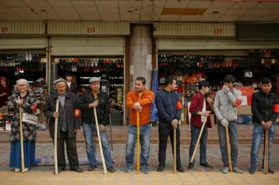 Shopkeepers line up with wooden clubs to perform their daily anti-terror drill outside the bazaar in Kashgar, Xinjiang Uighur Autonomous Region, China, March 24, 2017. REUTERS/Thomas Peter