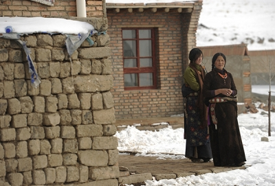 Two Tibetan women look out over the snow in Guoluo Tibetan Autonomous Prefecture in China. (Peter Parks/AFP/Getty Images)