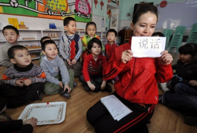 A Chinese teacher teaches Chinese characters to children at a kindergarten in Urumqi, capital of northwest China's Xinjiang Uygur Autonomous Region, Feb. 26, 2009. This kindergarten offers bilingual education to pre-primary school children of local Uygur people. (Xinhua/Zhao Ge)