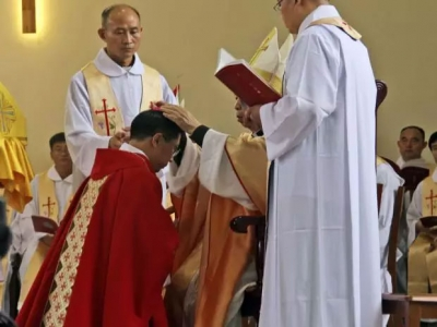 Rev. Joseph Zhang Yinlin, kneeling, takes part in an ordination ceremony to be named coadjutor bishop in Anyang city in central China's Henan province