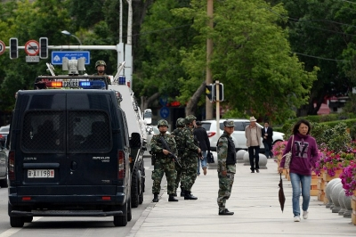 Fully armed Chinese paramilitary police officers stand guard along a street in Urumqi, May 23, 2014.