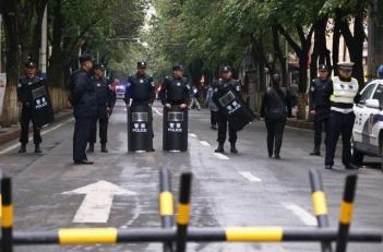 Policemen with riot gear stand guard behind a barricade near the site of an explosives attack in Xinjiang Uyghur Autonomous Region on May 23, 2014.