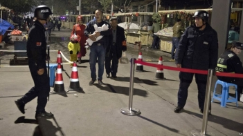 FILE - Residents walk past a security checkpoint at the close of a open-air market in Kashgar in western China's Xinjiang region, Nov. 4, 2017. Authorities are using detentions in political indoctrination centers and surveillance in efforts to control the Xinjiang region and its Uighurs, a Turkic-speaking Muslim minority Beijing fears could be influenced by extremism.