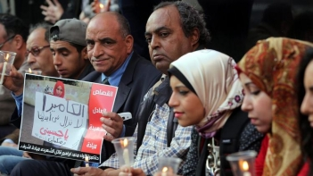 gyptian protesters hold candles and a poster depicting slain journalist Mayada Ashraf in Cairo this year. This is the sort of action that the Committee to Protect Journalists supports. (European Pressphoto Agency)