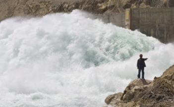 A worker directs a truck (unseen) as water gushes out from the Sangtuda-1 hydroelectric power plant in Tajikistan (May 28, 2008). Image Credit: REUTERS/Shamil Zhumatov