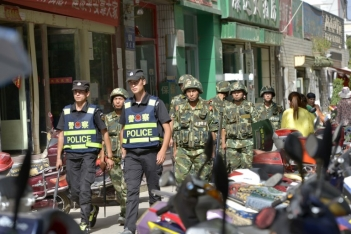 Chinese police officers and paramilitary policemen patrol a street in Kashgar city, July 23, 2014.