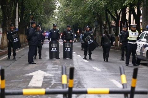 Policemen with riot gear stand guard behind a barricade near the site of an explosives attack in Xinjiang Uyghur Autonomous Region on May 23, 2014. Photo courtesy of HRW / © 2014 Reuters