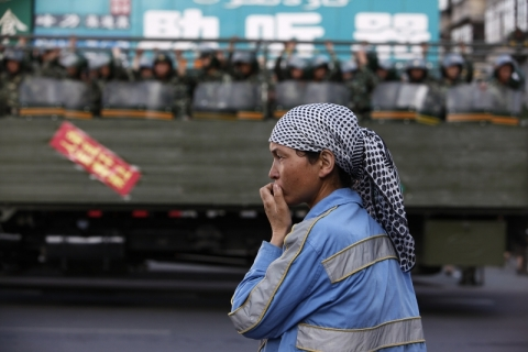 Chinese military police ride past a Uighur woman on main street in Urumqi, Xinjiang Uighur Autonomous Region, July 2009. (Nir Elias / Courtesy Reuters)