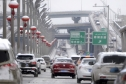 In this Monday, Feb. 20, 2017 photo released by Xinhua News Agency, vehicles run on the snow-covered road in Urumqi, capital of northwest China's Xinjiang Uygur Autonomous Region. A prefecture in China's Xinjiang region is requiring all vehicles to install satellite tracking systems as part of stepped-up measures against violent attacks. Traffic police in Bayingolin Mongol Autonomous Prefecture announced the regulation on Sunday, shortly after thousands of heavily armed police paraded in Urumqi and Communis