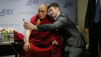 """Tibetan spiritual leader the Dalai Lama poses for a """"selfie"""" with blogger and activist Alek Boyd during a break between panel discussions at an event entitled: """"Happiness, Free Enterprise, and Human Flourishing"""" Thursday, Feb. 20, 2014, at the American Enterprise Institute in Washington."""
